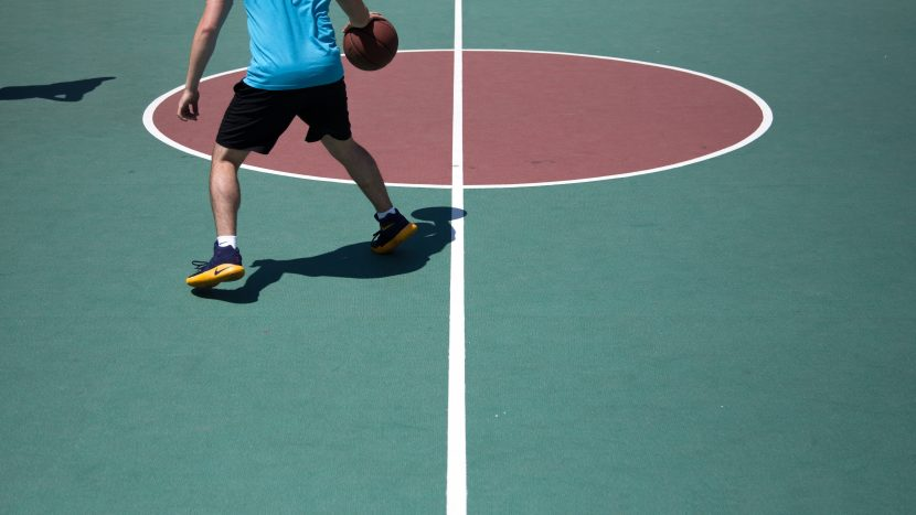 basketball player active on court. Basketball players may experience tendinopathy