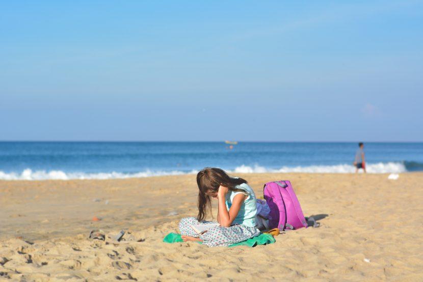 girl and schoolbag on beach