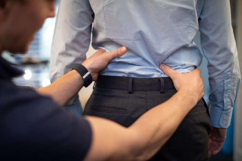Physio assessing low back of patient